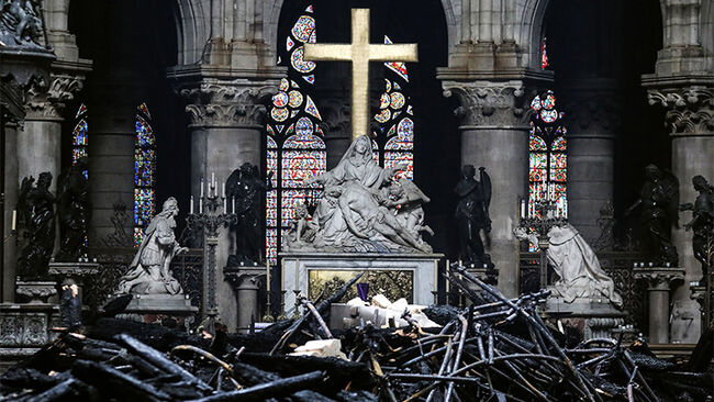 A picture taken on April 16, 2019 shows the altar surrounded by charred debris inside the Notre-Dame Cathedral in Paris in the aftermath of a fire that devastated the cathedral. - French investigators probing the devastating blaze at Notre-Dame