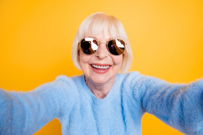 Close up portrait of happy grandma taking a selfie on vacation of two hands, isolated on yellow background