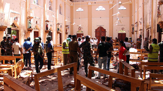 Sri Lankan security personnel walk through debris following an explosion in St Sebastian's Church in Negombo