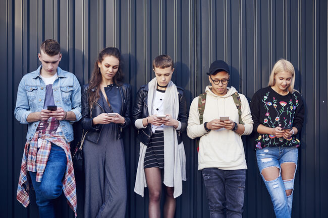 Row of five young adult friends leaning against black wall looking at smartphones