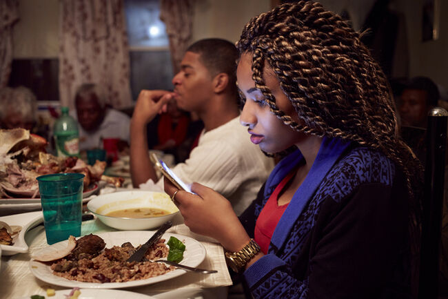 Teenage girl using cell phone at dinner table