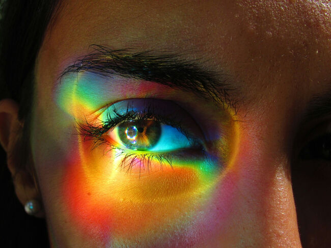 Close-Up Portrait Of Multicolored Light On Woman Eye