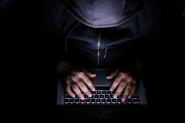 hacker Man with laptop stealing perdonal data from internet