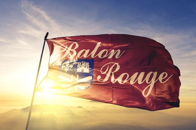 Baton Rouge city capital of Louisiana of United States flag textile cloth fabric waving on the top sunrise mist fog