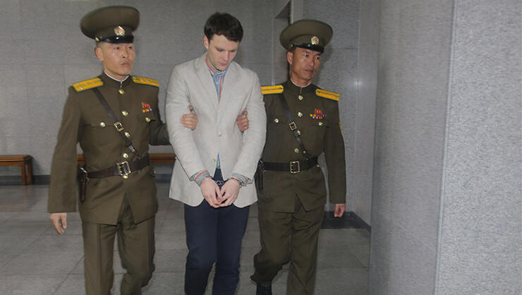 American student Otto Frederick Warmbier, center, arrives at a court for his trial in Pyongyang, capital of the Democratic People's Republic of Korea