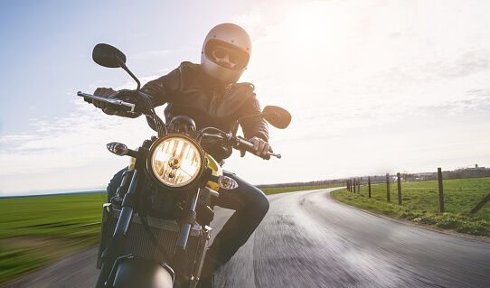 Portrait Of Mature Man Riding Motorcycle On Road