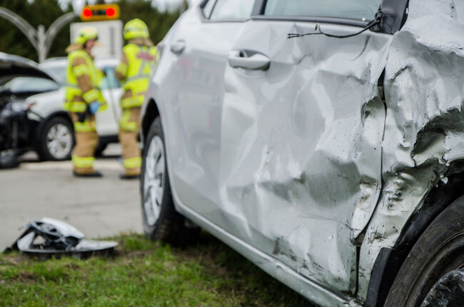Close up on a car crashed with fireman in background