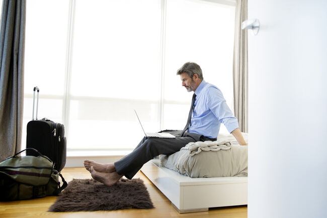 Businessman looking at laptop while sitting on bed at hotel