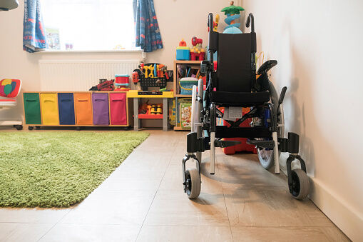 Empty wheelchair and colorful toys arranged at home