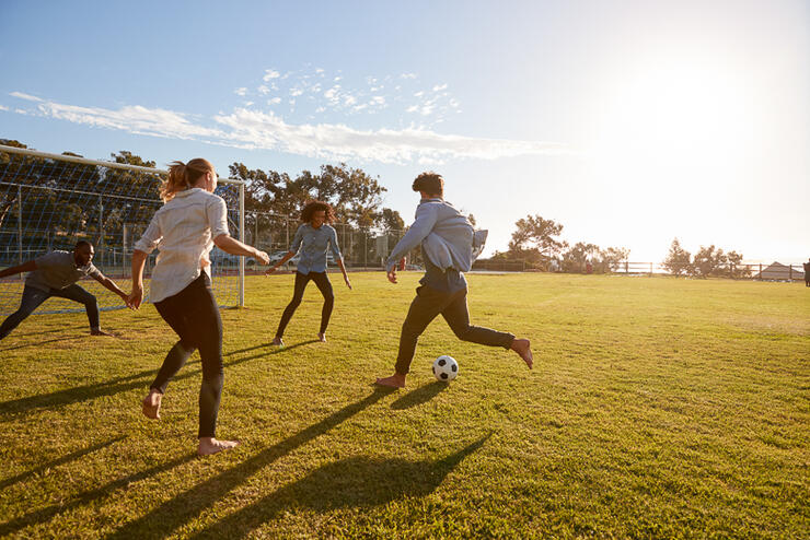 Four young adults playing football in a park at sunset