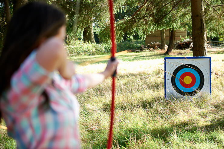 Rear view of teenage girl practicing archery with target