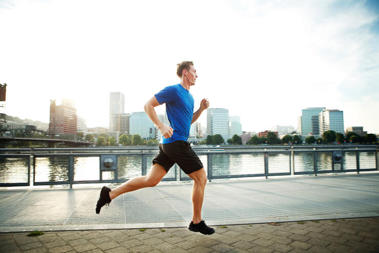 Young man jogging on promenade in city