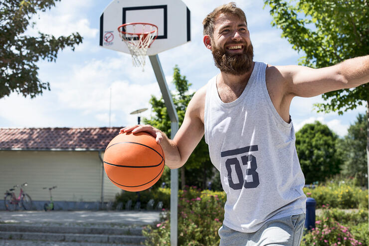 Laughing man playing basketball on outdoor court
