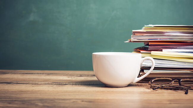 Coffee cup, papers stack on wooden school desk with chalkboard.