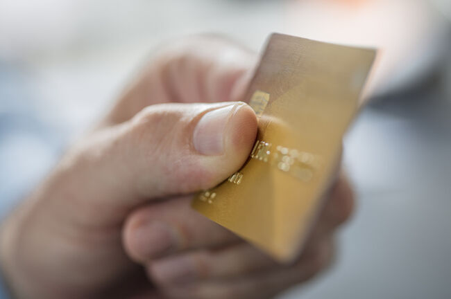 Man's hand holding credit card, close-up