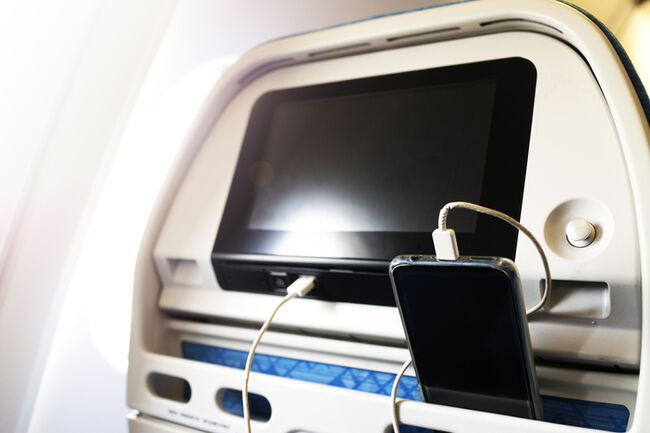 Passenger on a plane using the charger for charge smart phone during flight. Charging station on plane.