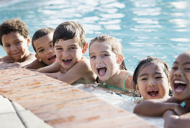 Multi-ethnic group of children on side of swimming pool