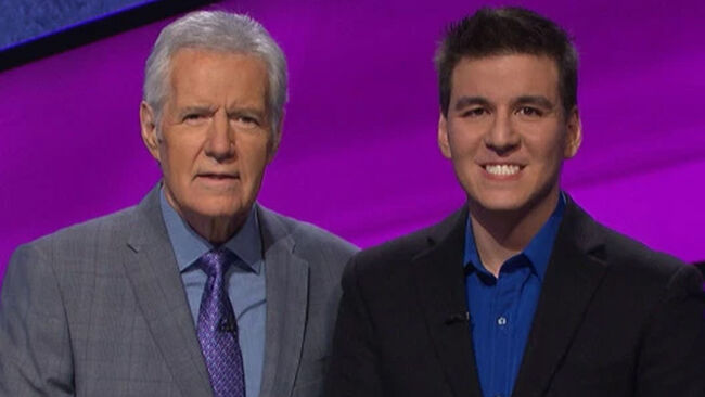 Jeopardy! host Alex Trebek standing with James Holzhauer