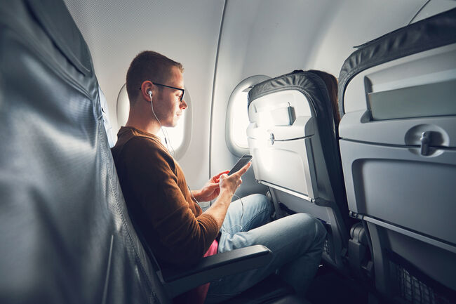 Man Listening Music While Using Mobile Phone In Airplane