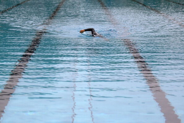 A lone swimmer in a wetsuit practices at