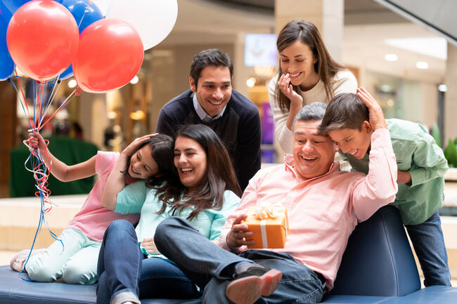 Happy grandfather celebrating Fatherâ??s Day with his family at the mall