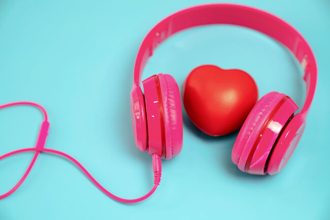 Red heart with headphones on blue background.