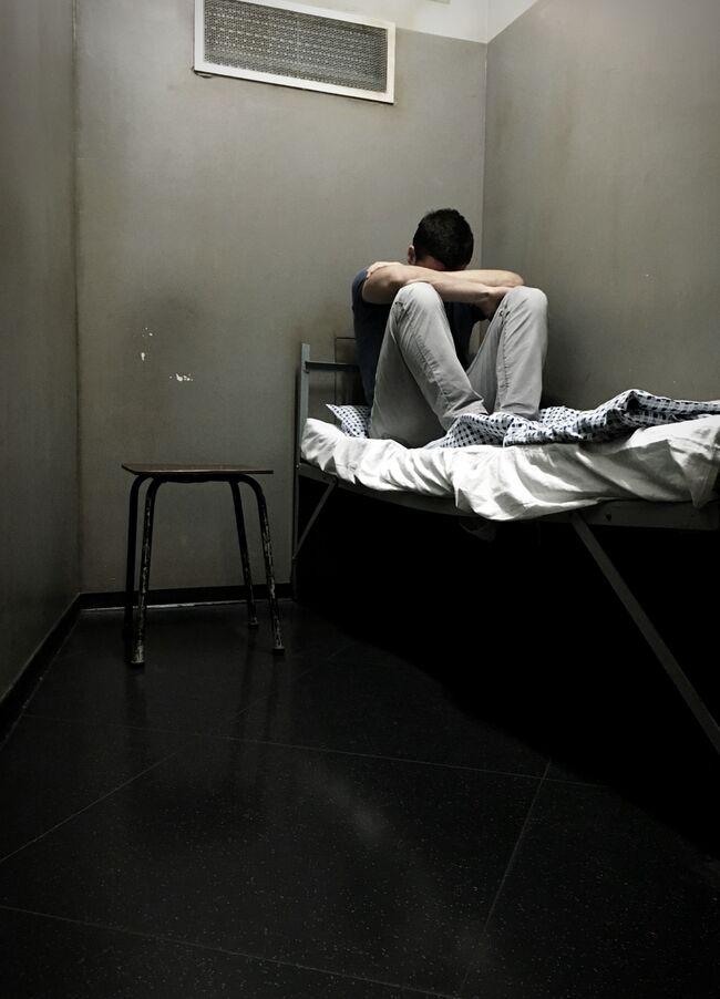 Male Prisoner Sitting On Bed In Prison