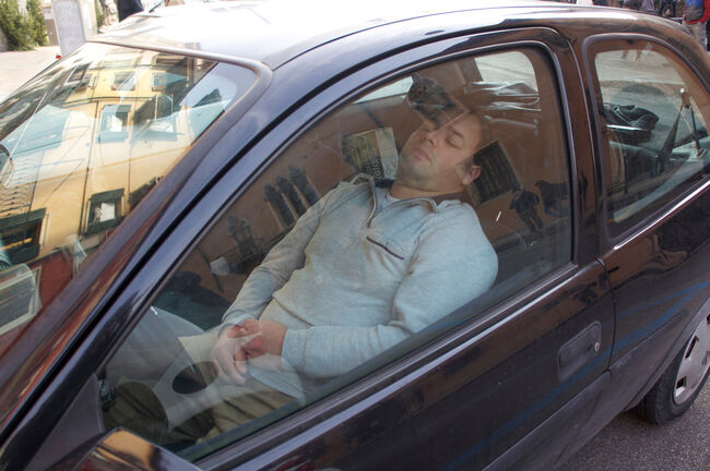 Man Sleeping In Car Seen Through Window