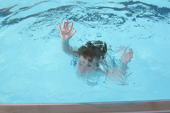 A person sinking in a swimming pool