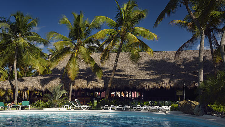 Pool and bar with coconut palm trees in Puerto Plata Dominican Republic
