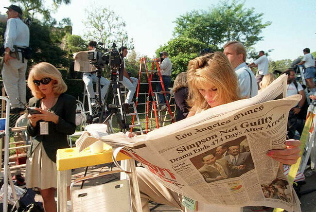 TV reporter Pat Lalama reads a newspaper headlinin