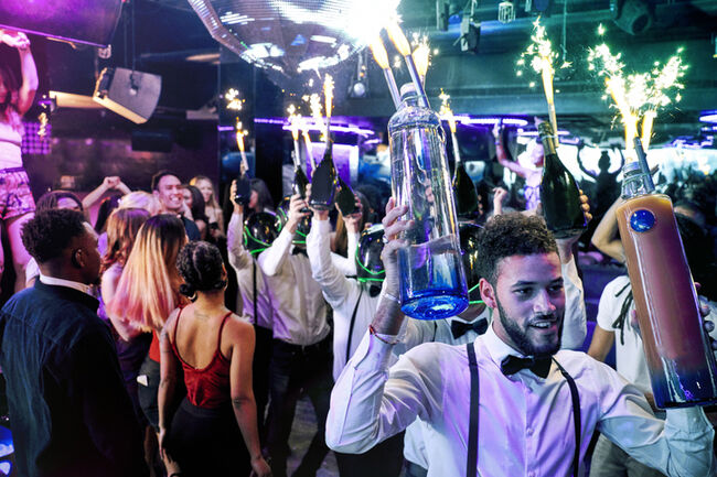 Bartenders with sparklers at nightclub
