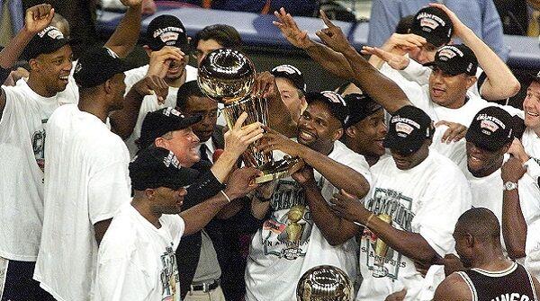 The San Antonio Spurs team gathers around the cham