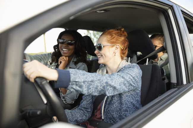 Smiling young women friends in car, enjoying road trip