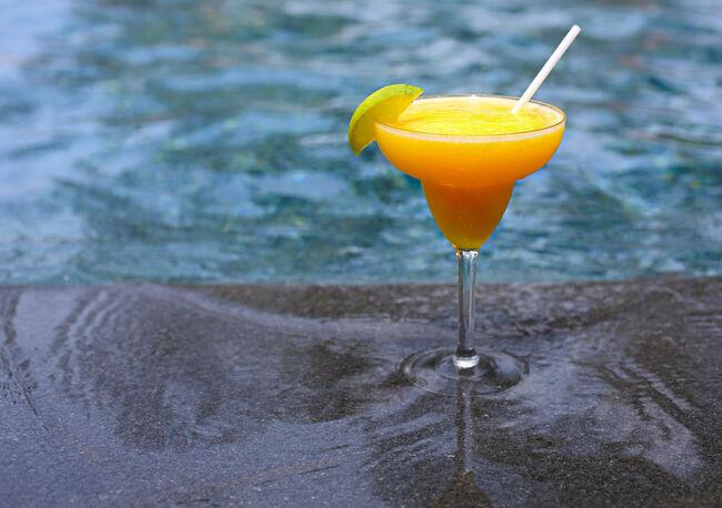 Mango daiquiri on the pool background