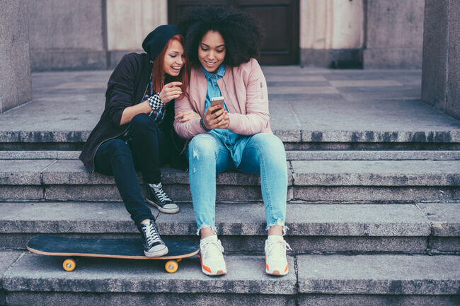 Teenage girls in the city texting on smartphone