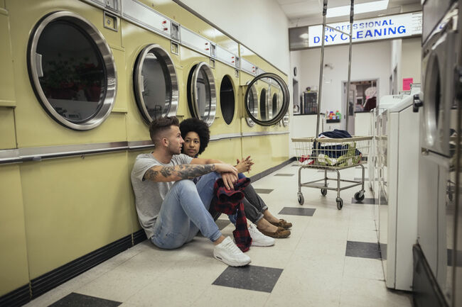 Young couple sitting and talking while waiting for laundry at laundromat
