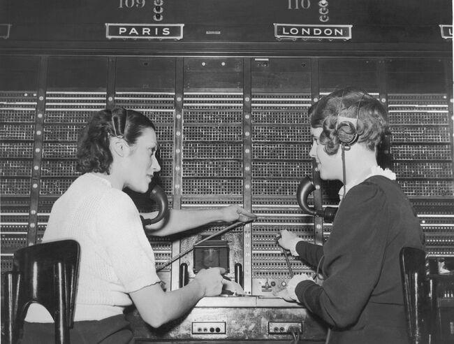Two female switchboard operators connecting international calls (B&W)