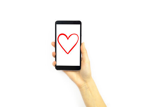 Hand holding a phone with a heart on it