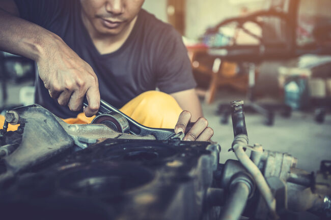 Midsection Of Male Mechanic Repairing Car In Workshop