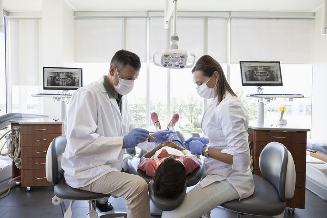 Dentist and dental hygienist checking teeth of boy in dentist office