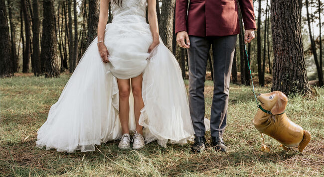 Low section of bride and groom in forest with funny dog-shaped balloon