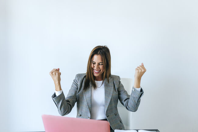 Business woman with expression of triumph in the office