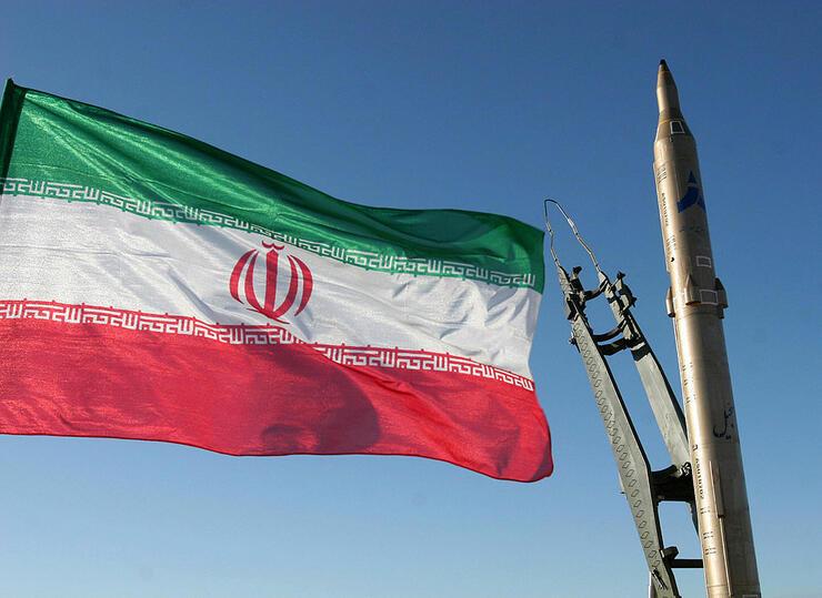 An Iranian flag flutters next to a groun