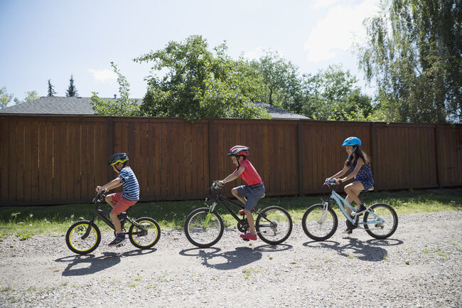 Boys and girl riding bicycles on sunny gravel road in a row