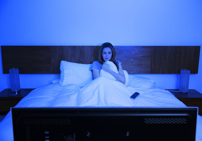 Woman watching television in bed