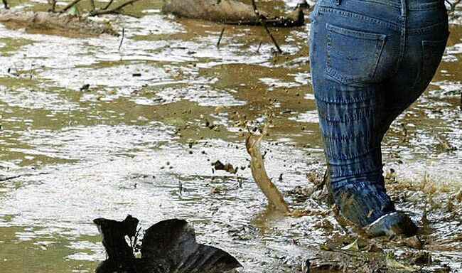 A woman tries to make her way in muddy w