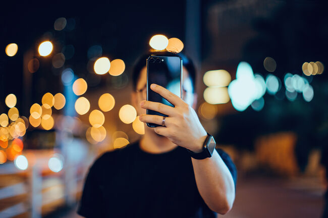 Smart young Asian man taking pictures with smartphone in city street, against illuminated city street light and city traffic