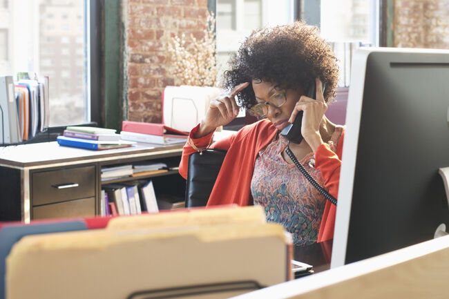 Black businesswoman talking on telephone at desk