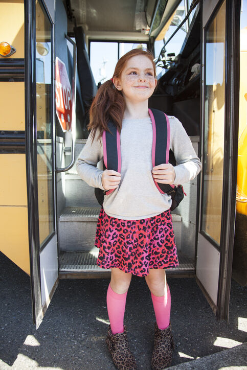 Happy girl with backpack at bus doorway